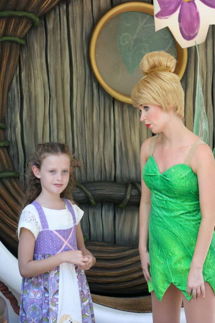 Girl talking to Tinker Bell at Disneyland