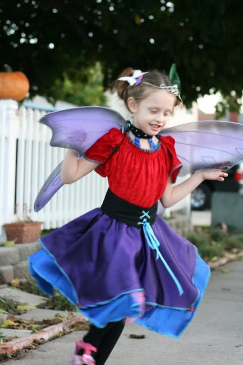 Girl twirling in a handmade fairy butterfly Halloween costume