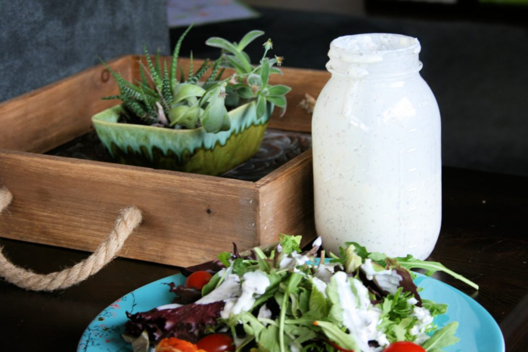 Creamy pesto salad dressing drizzled over greens and cherry tomatoes