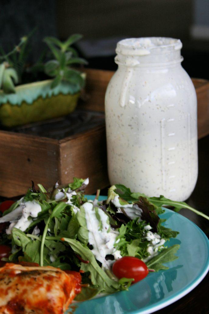 Creamy pesto dressing in Mason jar alongside salad greens and pizza slice