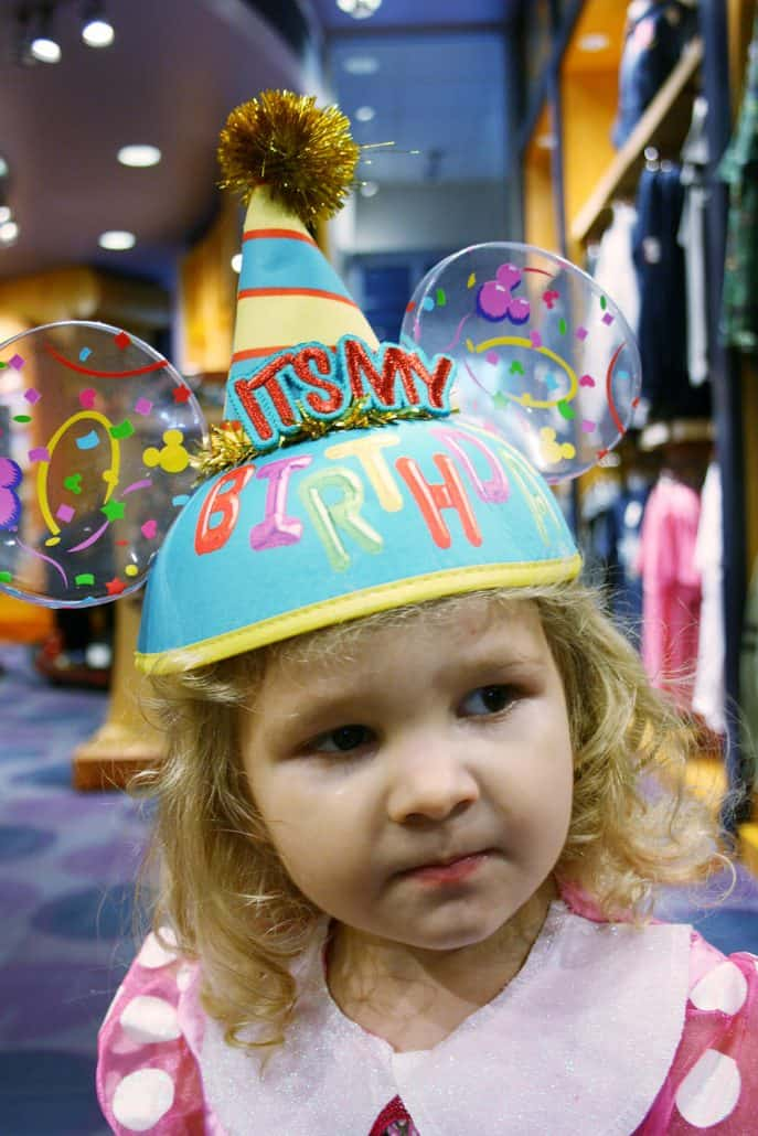 Little girl wearing a Disneyland Happy Birthday Mouse Ears hat
