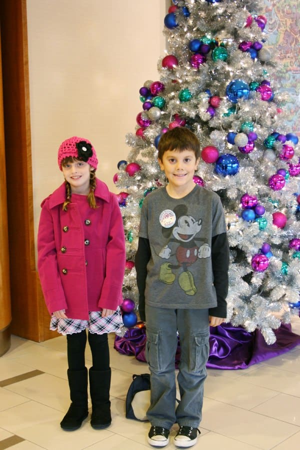Kids standing in front of retro Christmas trees inside Disneyland Hotel lobby