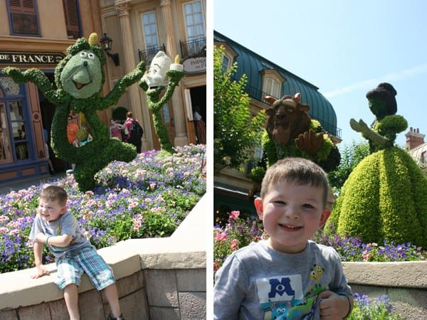Boy sitting in front of topiaries in France pavilion at Epcot flower and garden