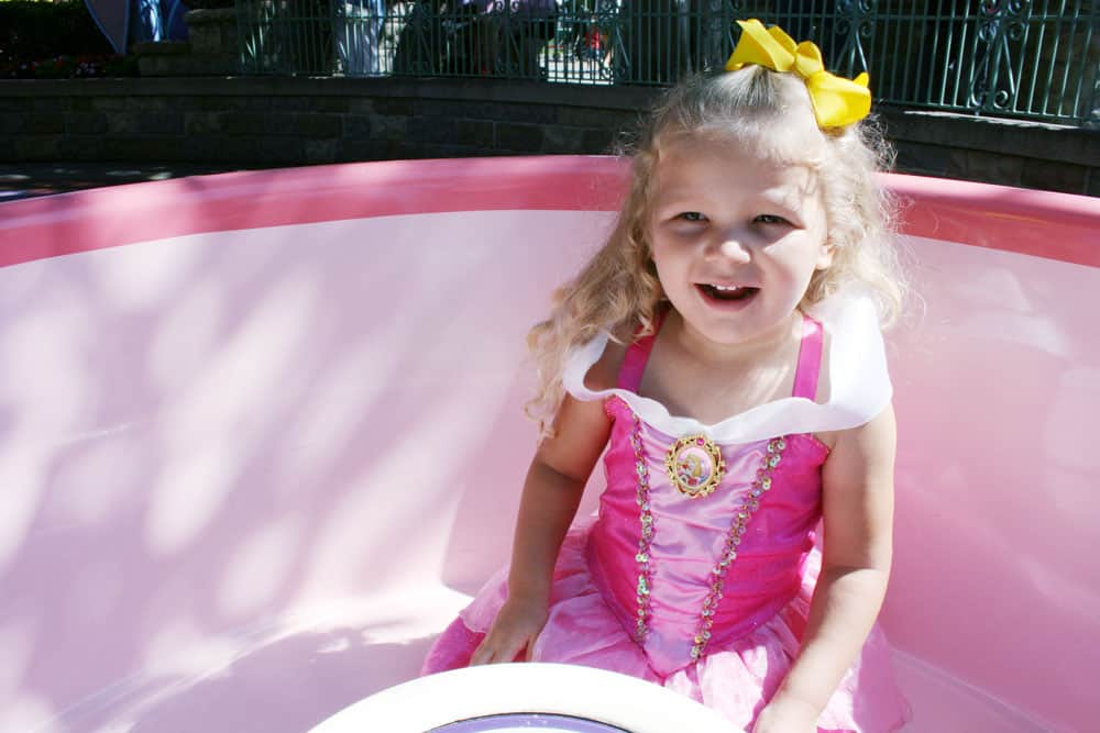 Girl dressed like Sleeping Beauty Aurora in Disneyland tea cup