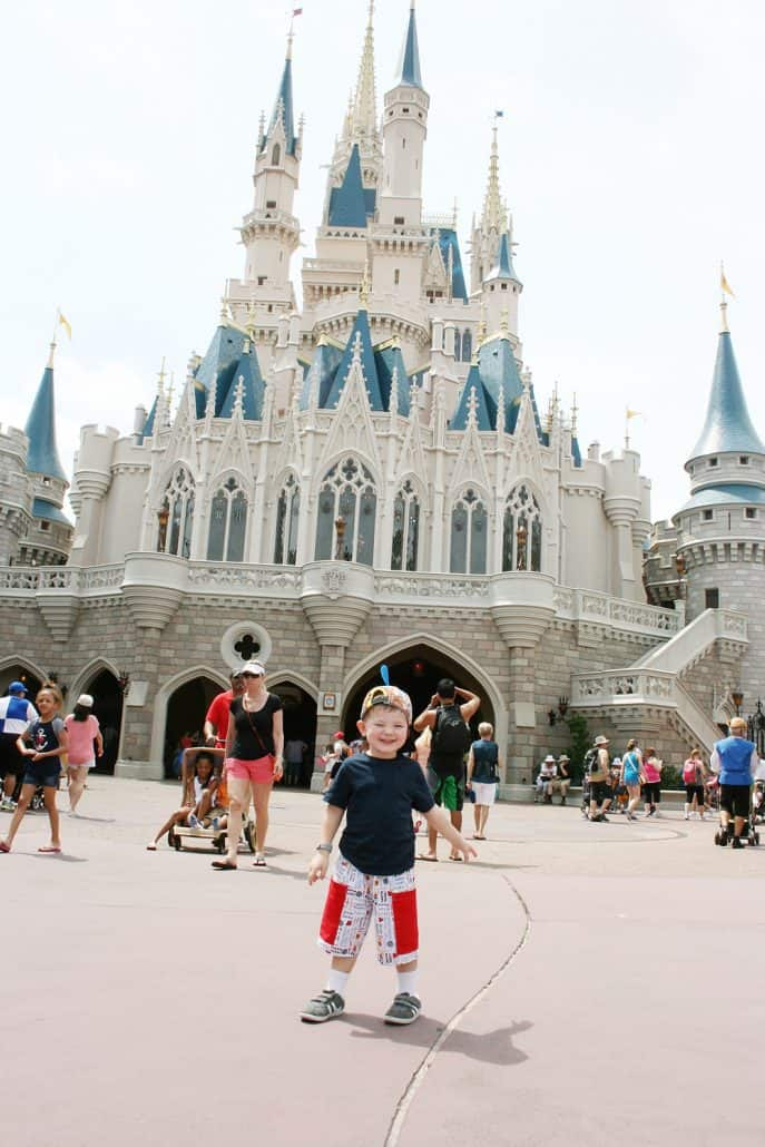 Cinderella Castle at Walt Disney World Magic Kingdom with a toddler standing in front
