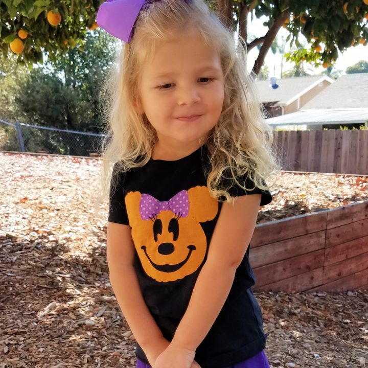 Little girl with purple bow wearing a Halloween Minnie Mouse t shirt