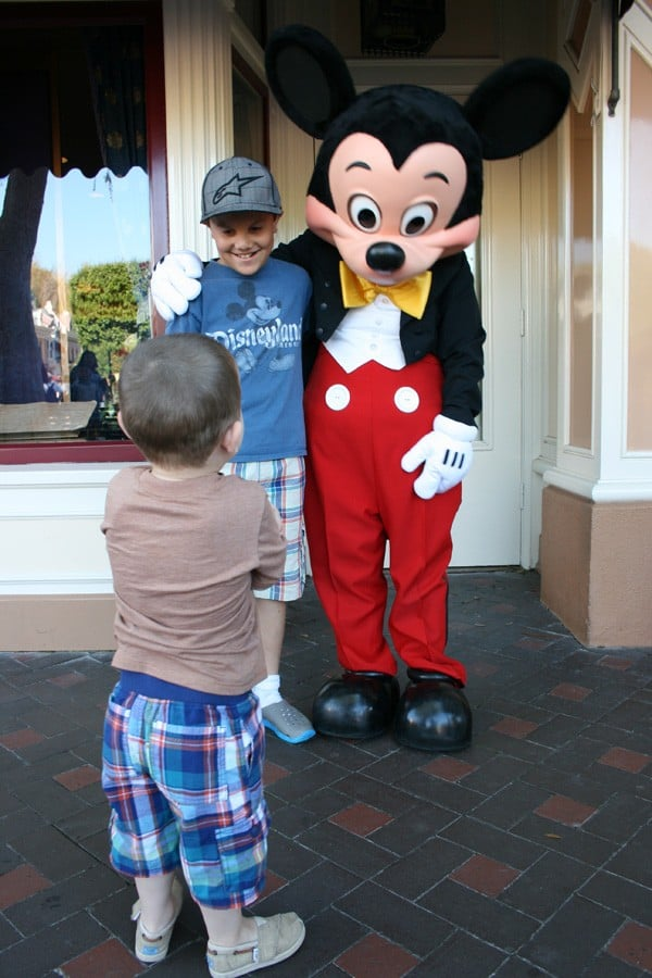 Kid standing with Mickey Mouse at Disneyland