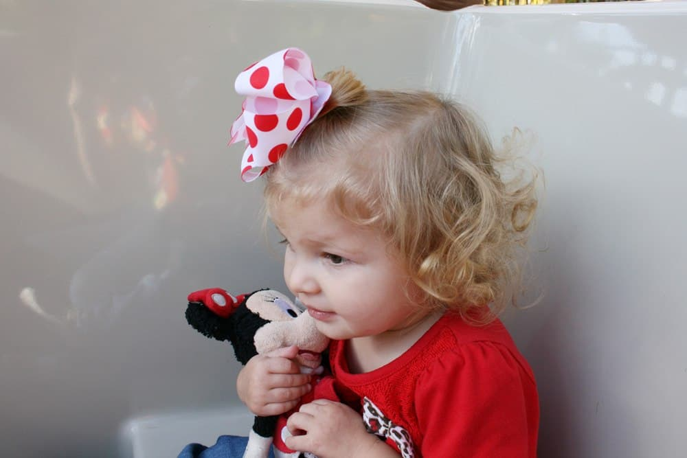 Scared girl holding Minnie doll at Disneyland