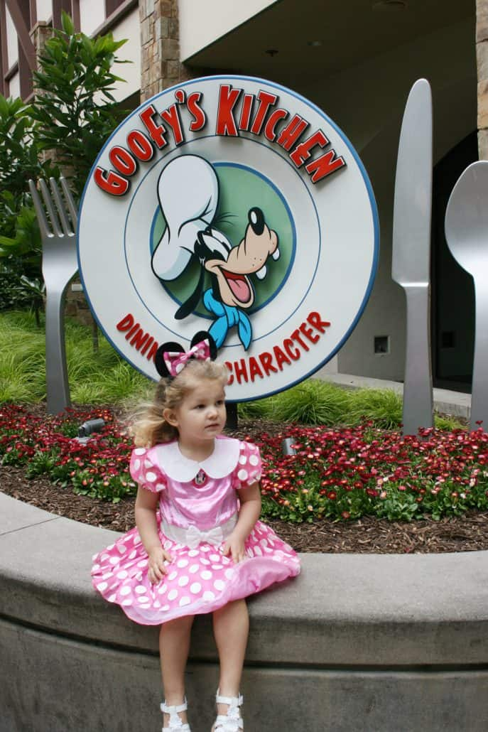Child in a Minnie Mouse dress sits outside Goofy's Kitchen at the Disneyland Hotel