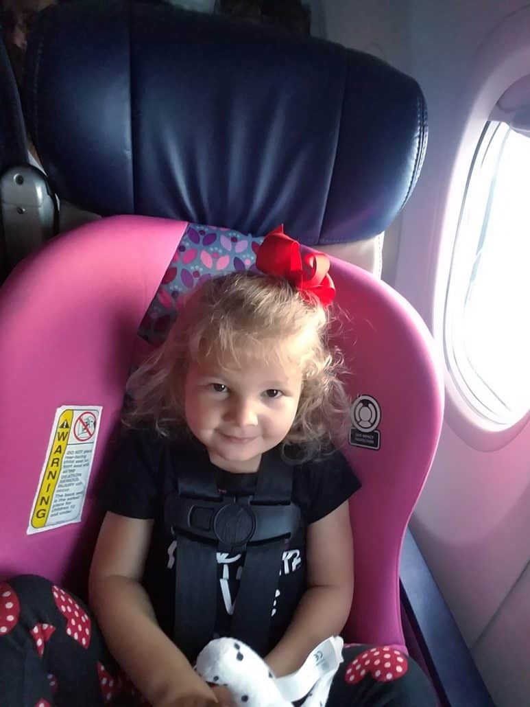 Child in pink Costco Scenera car seat on an airplane