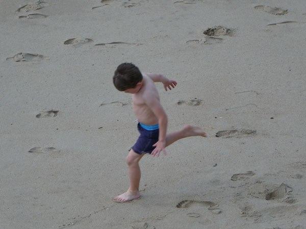 Boy running by himself on the beach