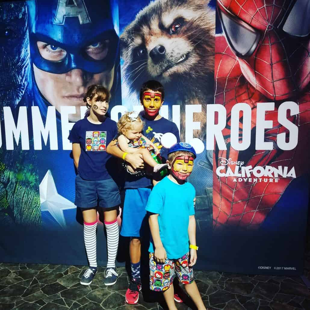 Kids standing in front of sign at Disneyland for Summer of Heroes