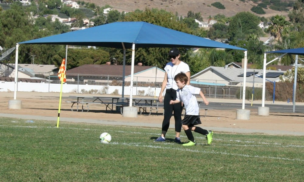 Women on soccer field coaching a child