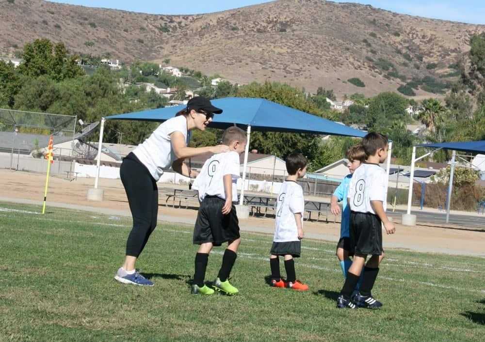 Mom soccer coach talking to players on the team