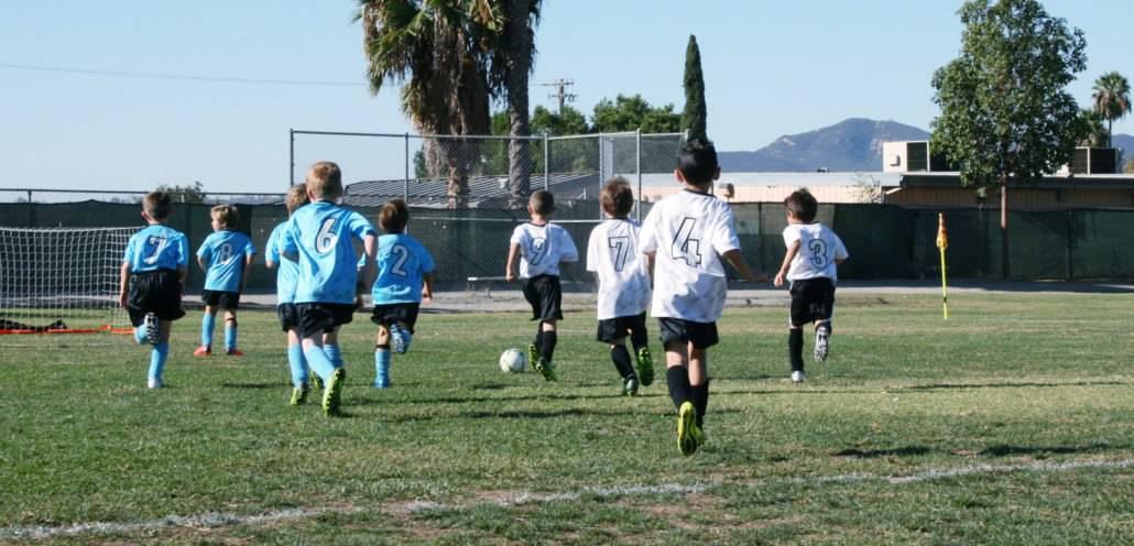 boys on a soccer field running towards the ball