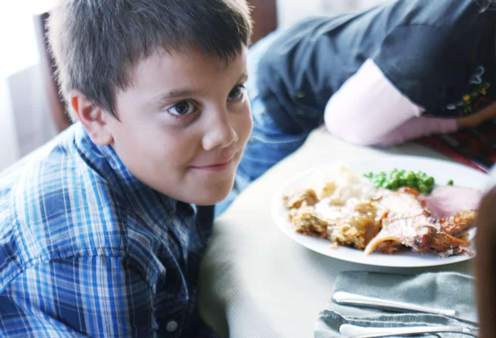 boy sitting at thanksgiving dinner table