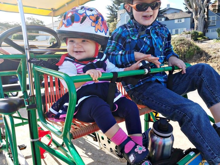 Toddler and kid riding in a bike, wearing helmets