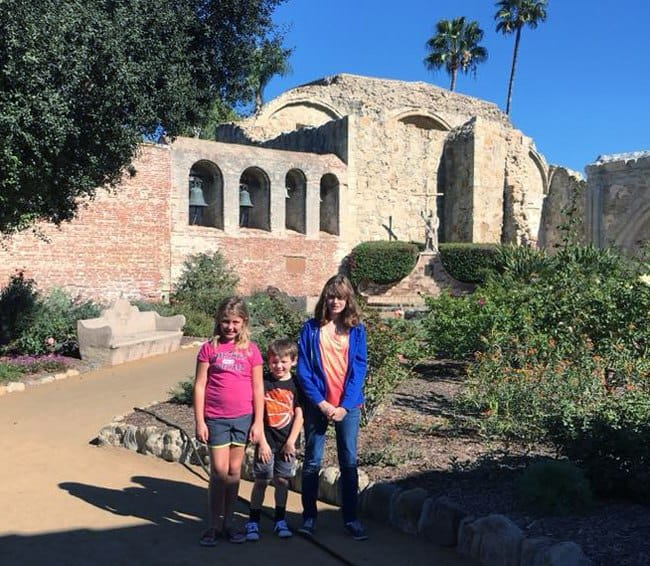 Mission San Juan Capistrano in Southern California with kids in front