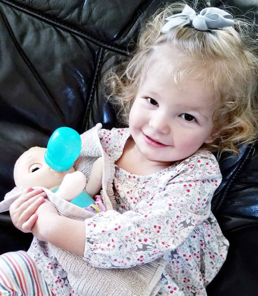 Toddler girl holding a baby doll