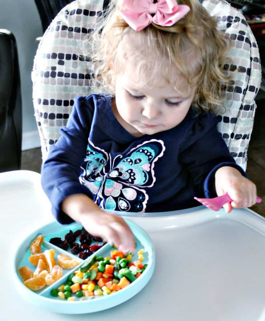 Toddler eating off a plate of food