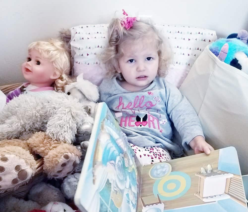 Toddler in bed with a book and stuffed animals