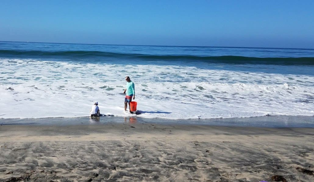 Father and son on a beach in Carlsbad California collecting water for a sand castle