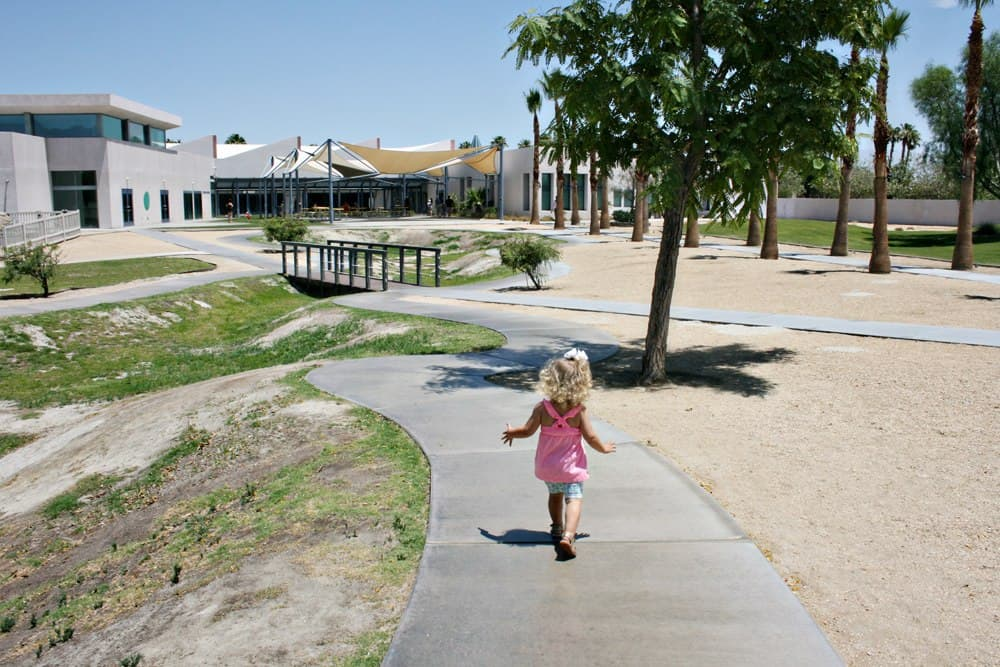 Toddler walking outside at a Palm Springs children's museum