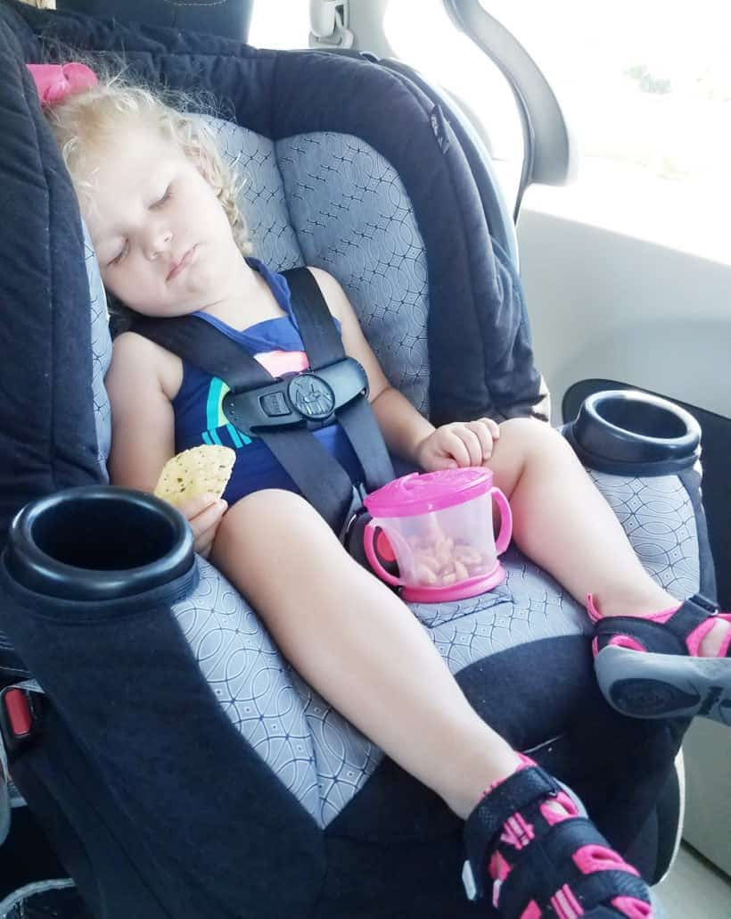 Toddler asleep in her car seat holding a tortilla chip