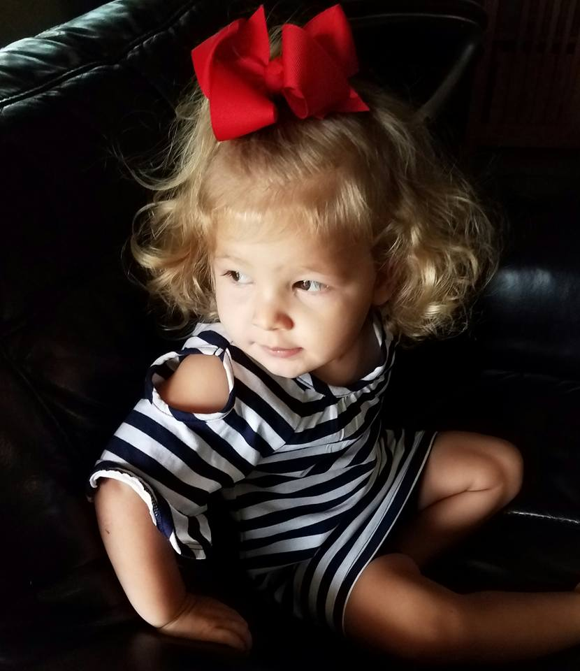 Toddler wearing a striped dress and red bow