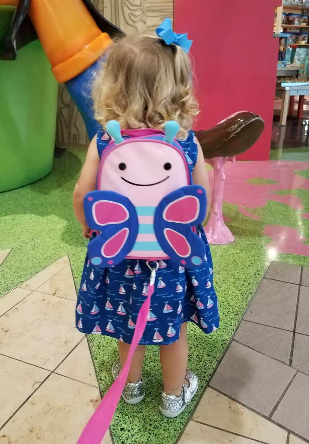 Toddler wearing a Skip Hop butterfly backpack with harness