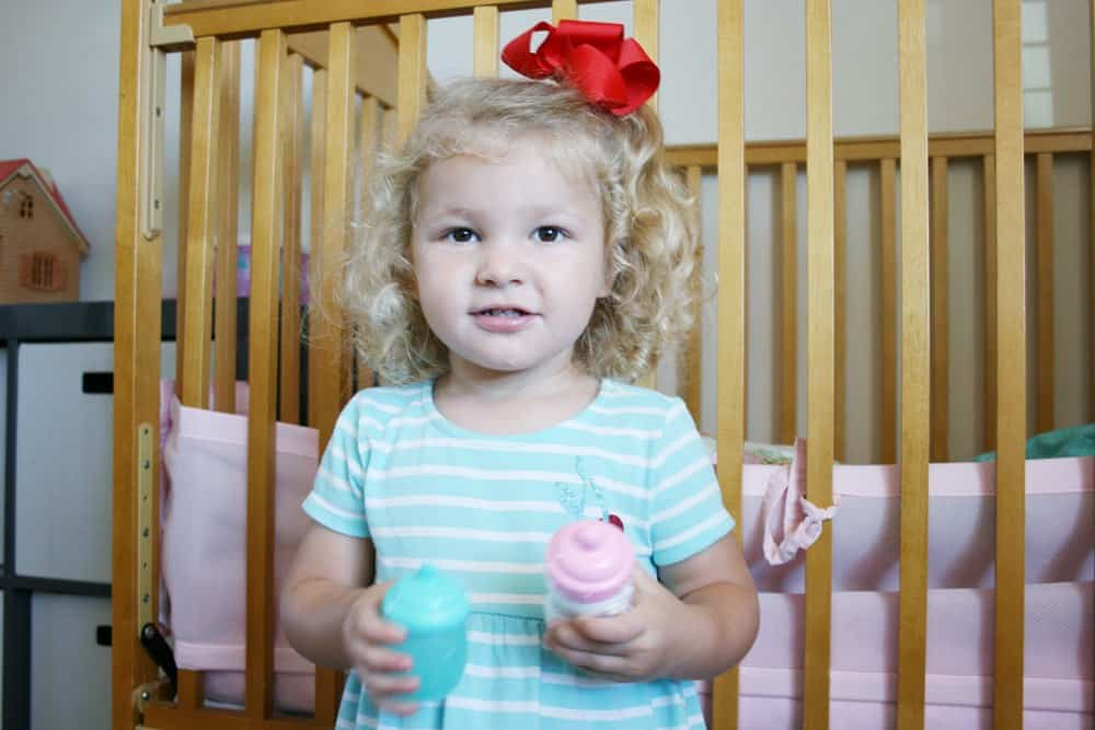 Toddler girl holding toy baby bottles