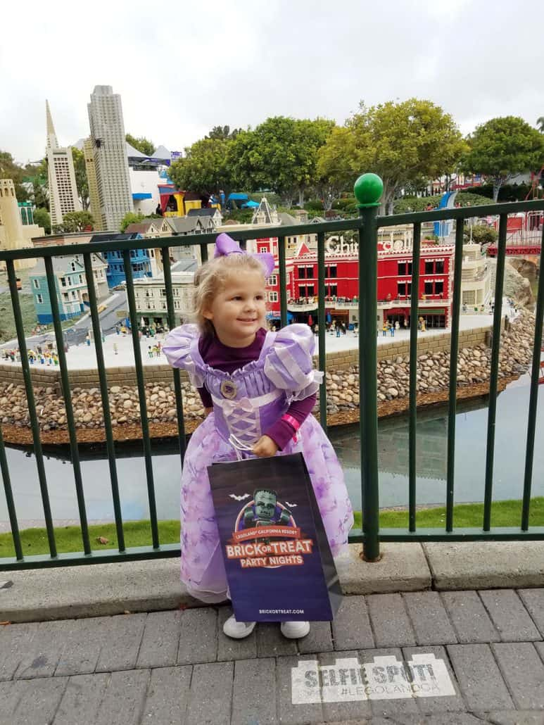 Little girl in Rapunzel Halloween costume at LEGOLAND Brick-or-treat party night