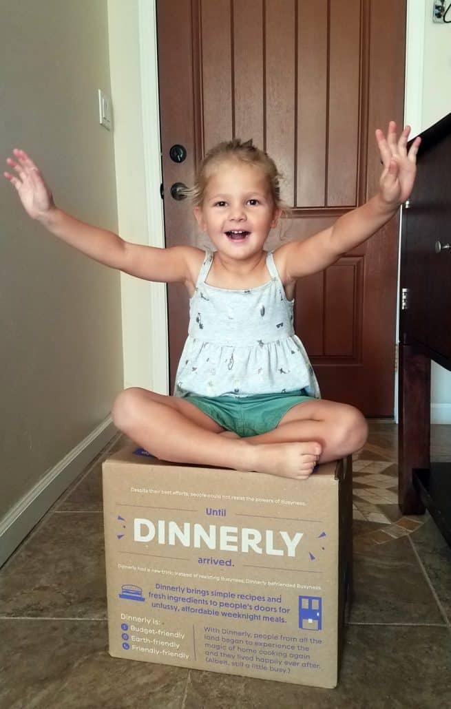 Little girl sitting on Dinnerly meal kit box