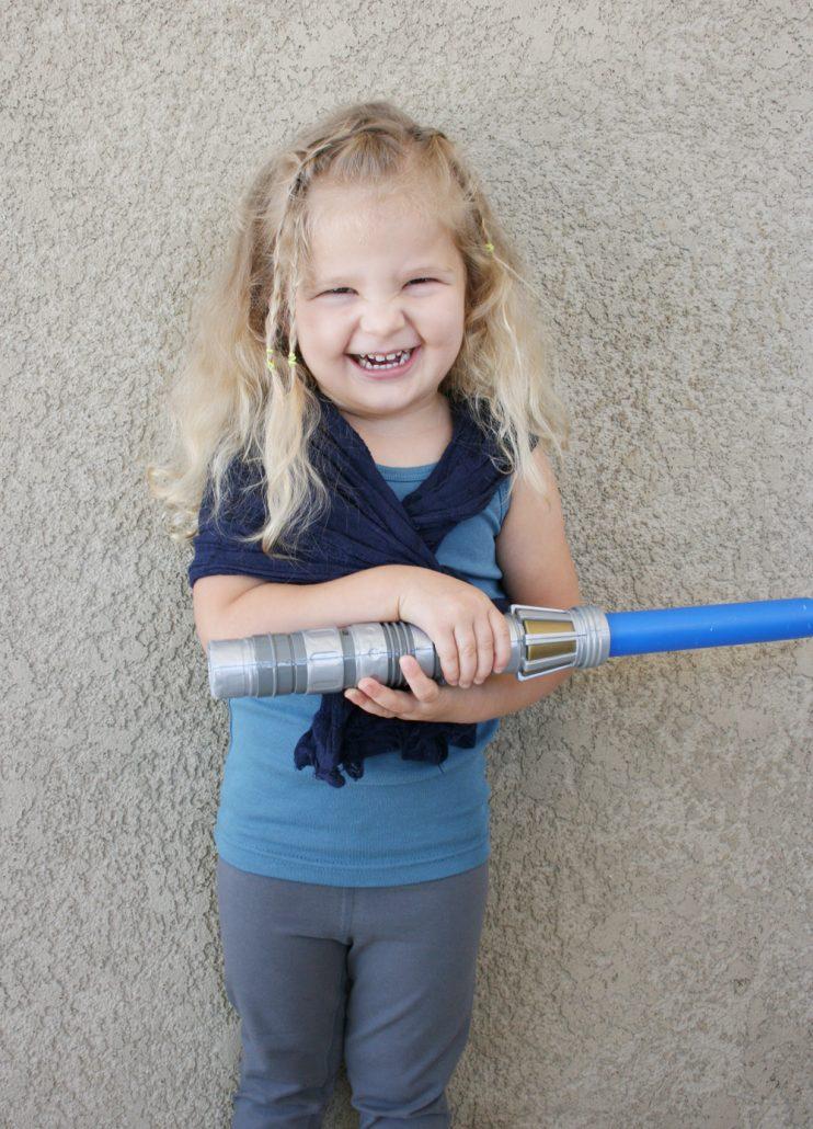 Preschool girl holding a light saber