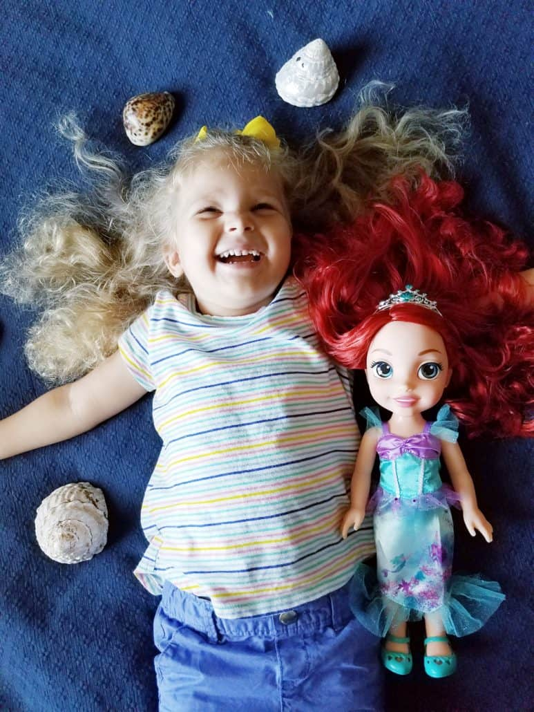 Little girl with Ariel doll