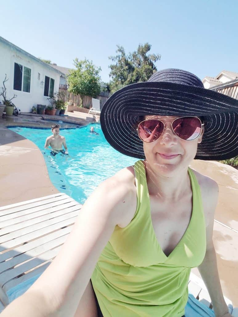 Woman in sun hat sitting near the pool
