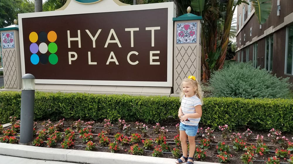 Hyatt Place Anaheim Resort sign in front with little girl