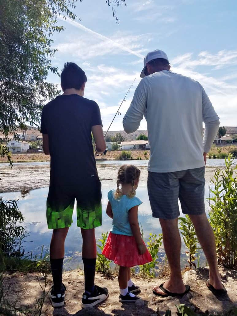 Teenager, little girl and dad fishing at the lake