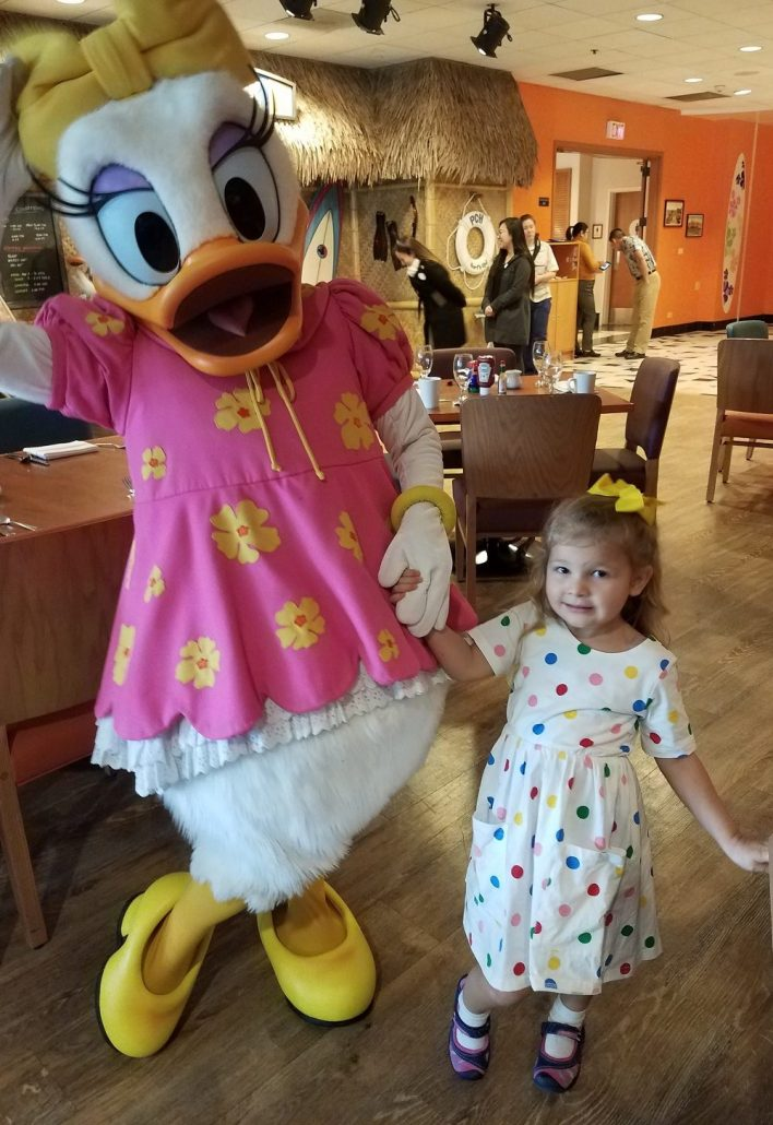 Little girl posing with Daisy Duck during Donald Duck's Seaside Breakfast