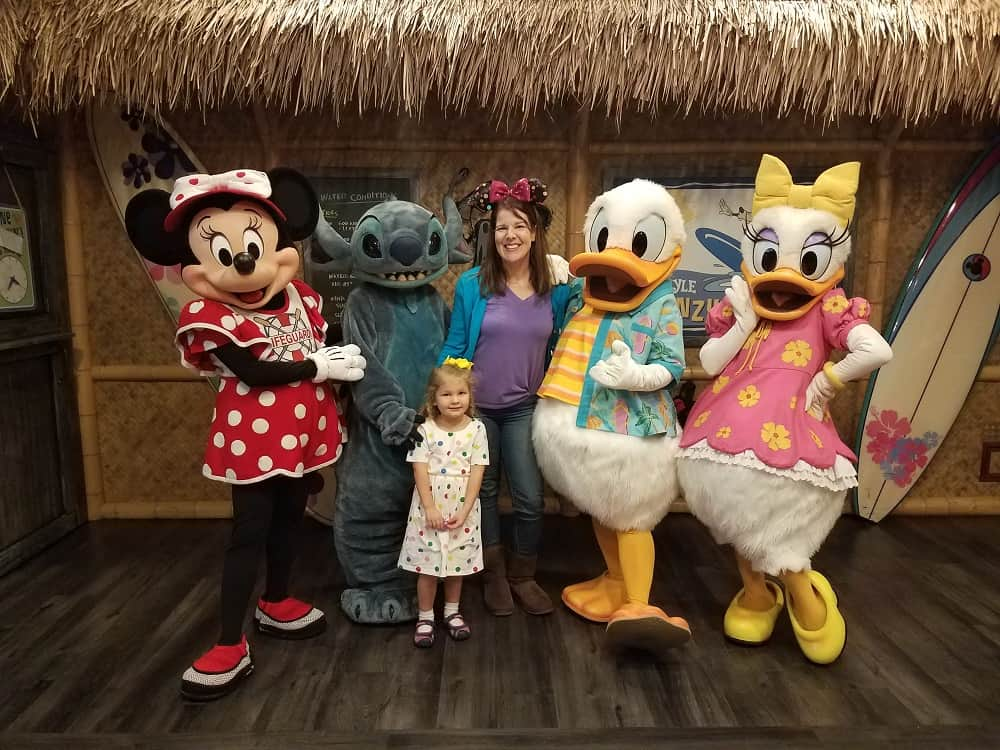 Minnie, Stitch, Donald and Daisy pose with mom and girl at Donald Duck's Seaside Breakfast