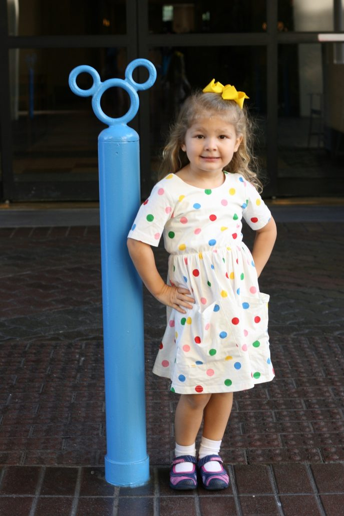 Little girl posing at Paradise Pier hotel wearing a polka dot dress