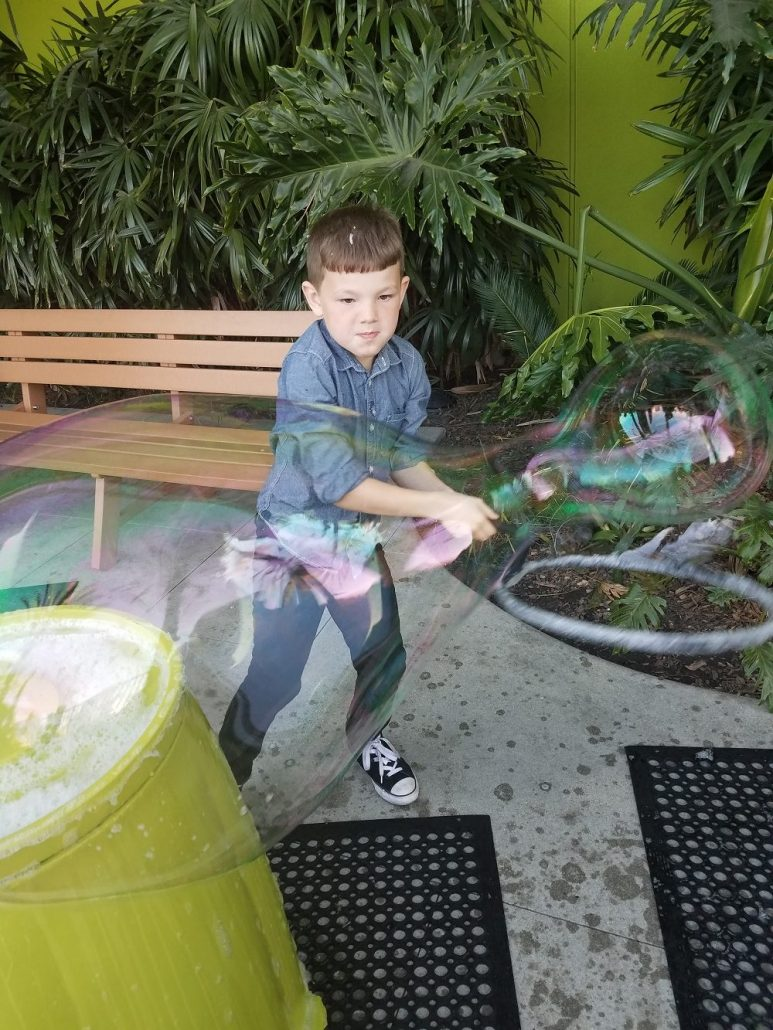 Kid making huge bubbles at Bubblefest Discovery Cube OC