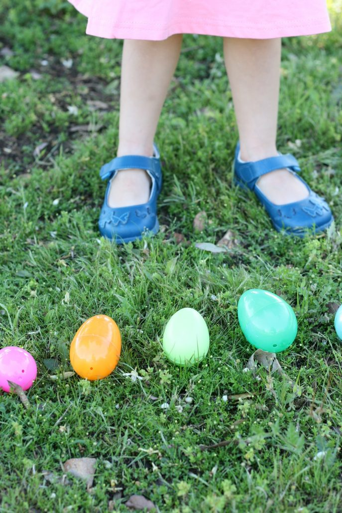 Little girl shoes standing in grass with Easter eggs