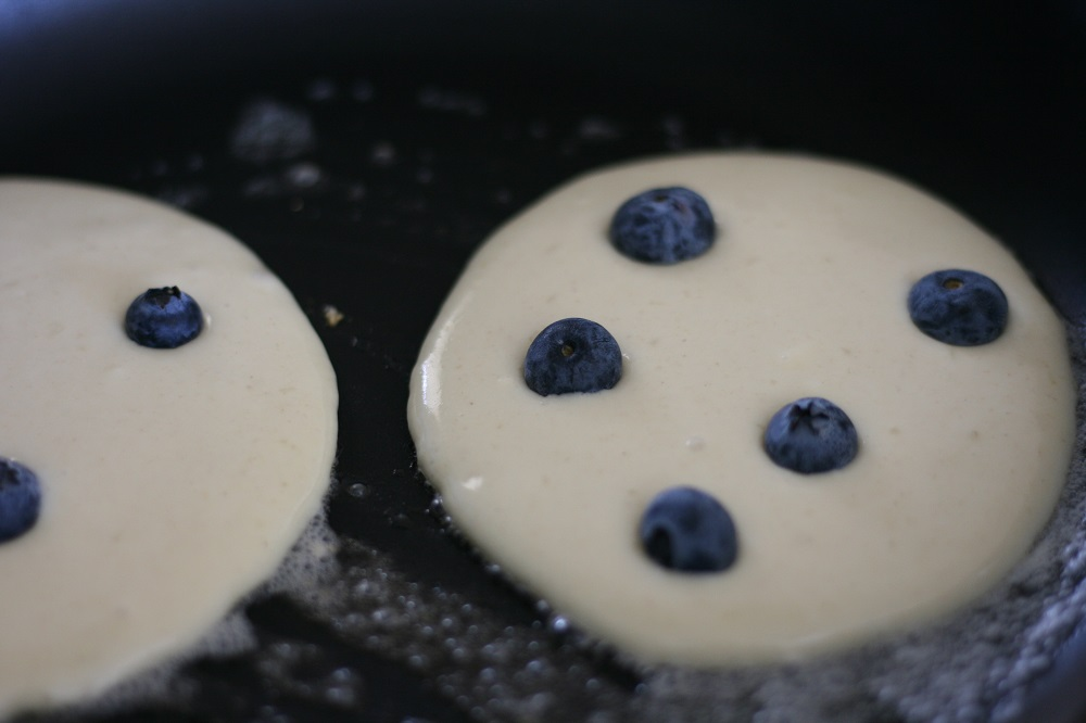 Blueberry pancakes cooking on the stove griddle