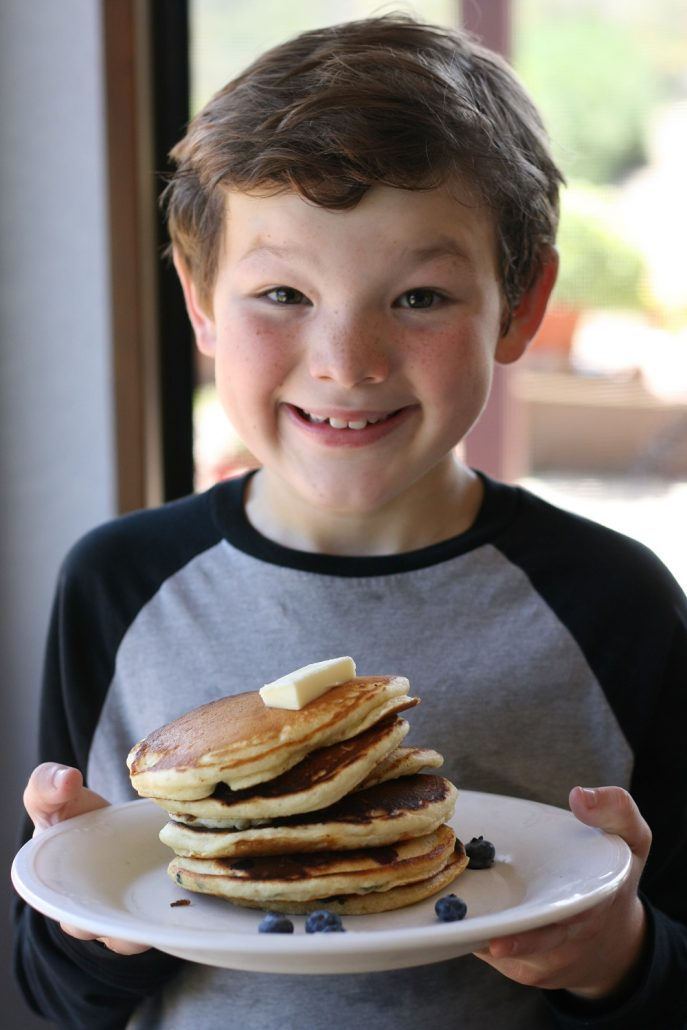 Little boy holding a stack of pancakes on a plate