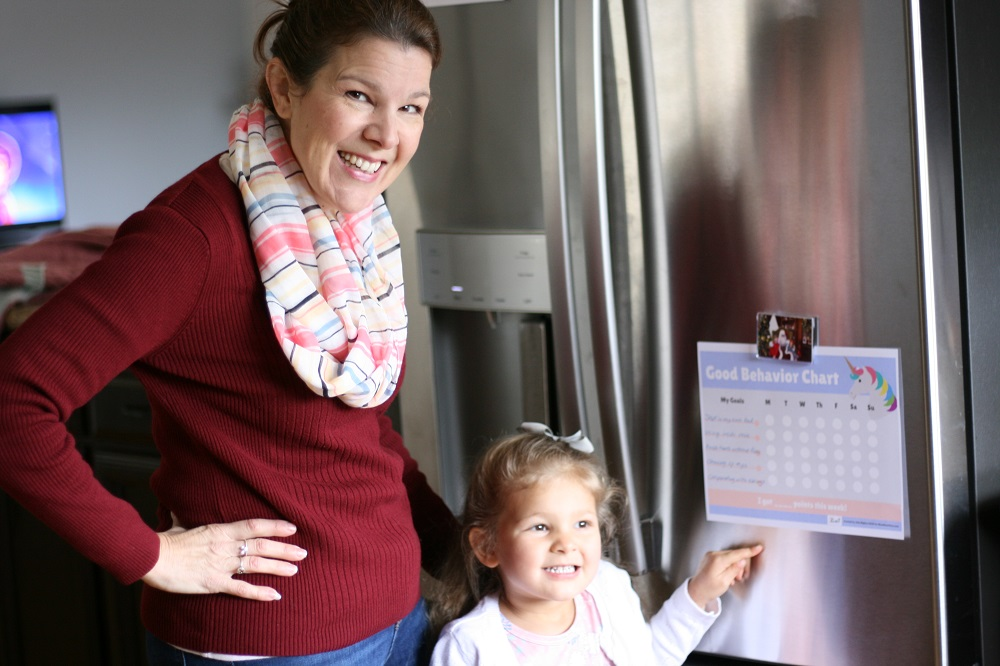 Mom and daughter look at behavior chart on the fridge