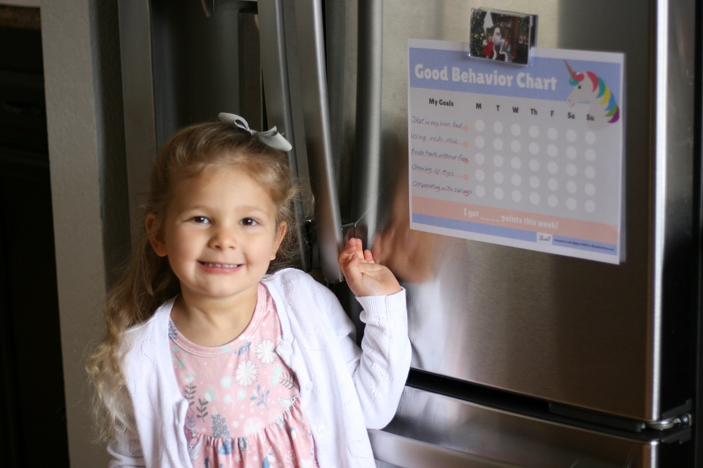 Little girl standing at fridge next to a printed behavior chart