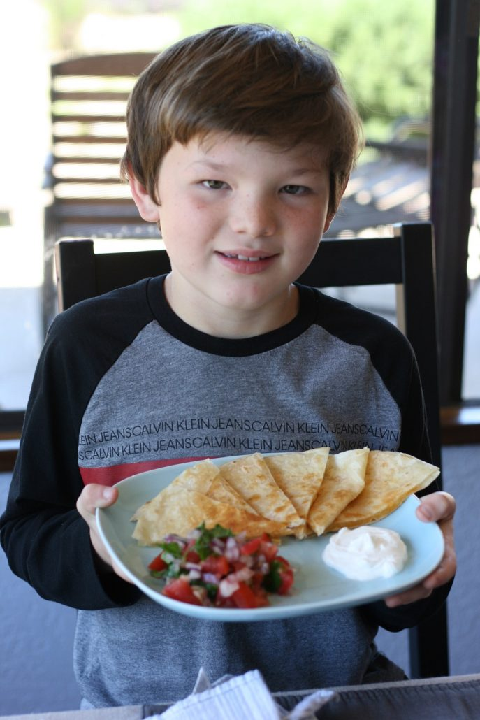 Boy holding plate with quesadillas and salsa