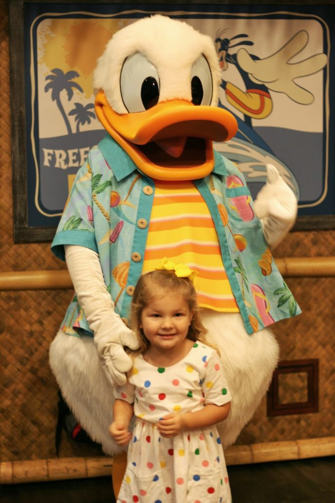 Little girl standing with Donald Duck at Seaside Breakfast
