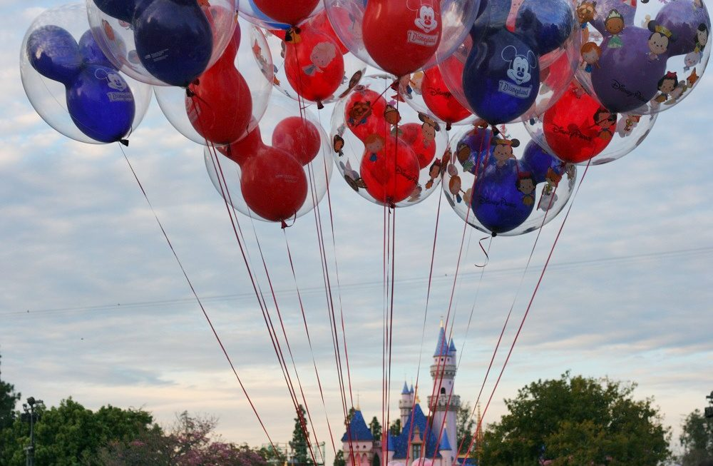 Red and purple Mickey balloons at Disneyland with Sleeping Beauty Castle in background